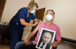 Чиновник из Аргентины привился от коронавируса с портретом Путина в руках